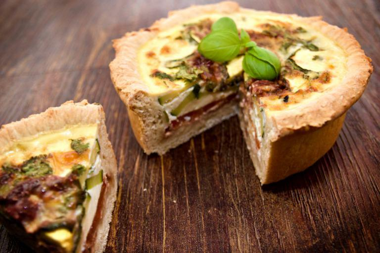 A delicious deep layered Mediterranean quiche with basil garnish